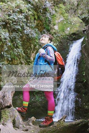 Amüsiert junge Frau Wanderer in der Nähe von Wasserfall