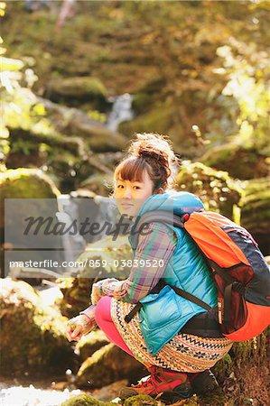 Jeune femme assise près de cours d'eau