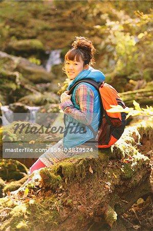 Jeune femme randonneur assis sur bois souriant