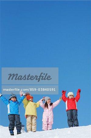 Enfants debout dans la neige avec bras levé