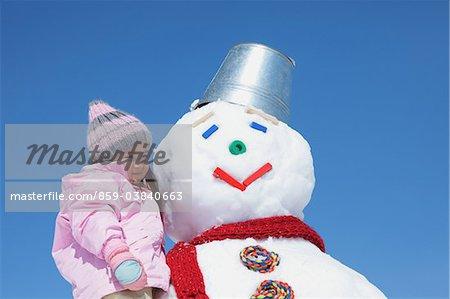 Petite fille debout de bonhomme de neige