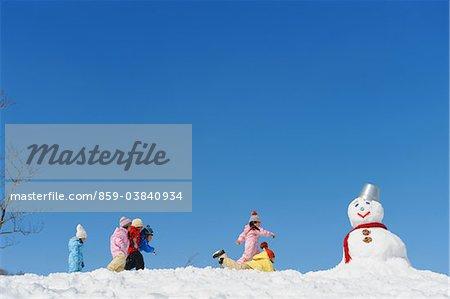 Enfants avec bonhomme de neige dans la neige