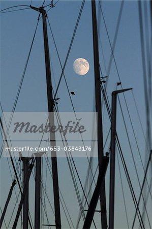 Les mâts des voiliers, aube, lune en arrière-plan