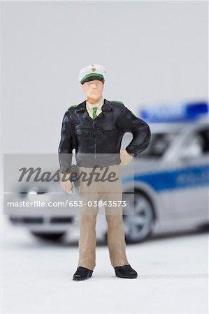 Un standing de figurine miniature policier par une voiture de police miniature