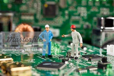 Deux hommes de figurine miniature travaillant sur une carte mère de l'ordinateur