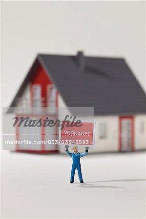 Une figurine de travailleur de construction miniature tenant en altitude un signe VERKAUFT (vendu en allemand)