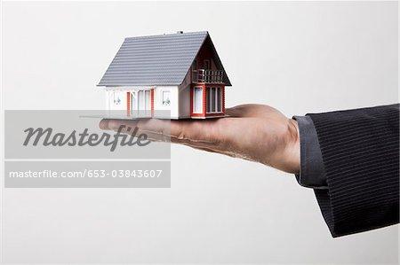 Mann, der zu Hause in seine Handfläche Miniatur