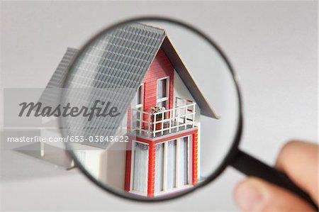 Ein Modell-Haus durch eine Lupe betrachtet