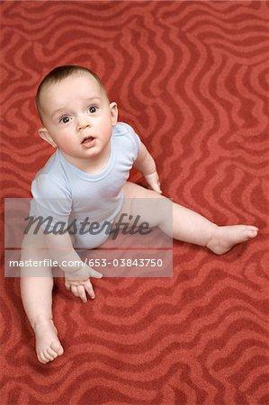 Un petit garçon assis sur un tapis à motifs