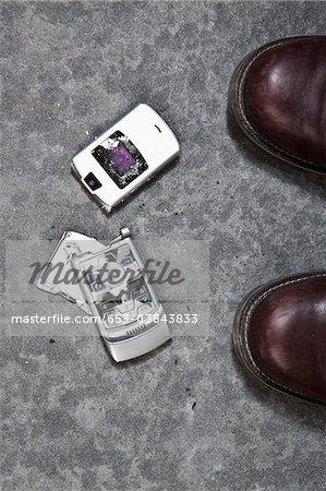 Deux démarré pieds à côté d'un téléphone portable brisé