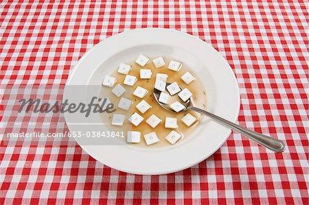 Un bol de soupe avec des touches d'un clavier flottant dedans