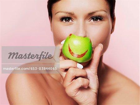 Eine Frau hält einen grünen Apfel mit leuchtend roten Lippenstift drauf