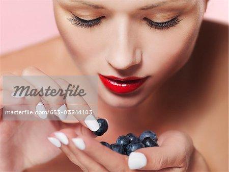 Eine Frau, die ihre Handfläche eine Heidelbeere auswählen