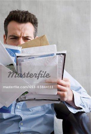 Er hält ein Mann schielen auf ein Bündel von mail