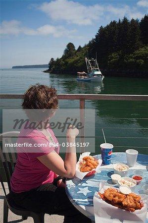 Femme regarder les bateaux de pêche dans le chenal de l'île proche tout en mangeant un repas de fruits de mer à la maison de chaudrée de côté canal à Kodiak, l'île Kodiak, Alaska sud-ouest, été