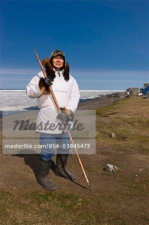 Porträt eines männlichen Inupiak Eskimo-Jägers seine Eskimo Parka (Atigi) und Siegel Haut Hut tragen und halten einen Gehstock bei alten Utkeagvik Stadt Originalstandort mit Blick auf die Tschuktschensee, Barrow, Alaska Arktis, im Sommer