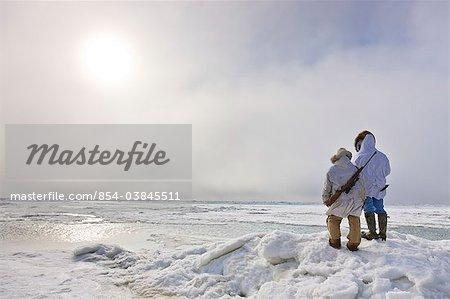 Male and female Inupiaq Eskimo hunters wearing their Eskimo parka's (Atigi) carry a rifle and walking stick while looking out over the Chukchi Sea, Barrow, Arctic Alaska, Summer