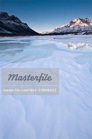 Alpenglühen am Boreal Mountain spiegelt auf Überlauf Eis auf der North Fork des Koyukuk River in Gates Arctic National Park & Preserve, Arktis, Alaska, Winter
