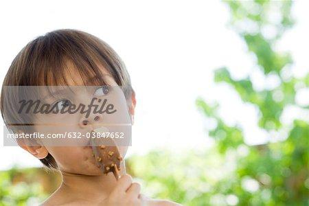 Petit garçon mangeant de la crème glacée bar, portrait