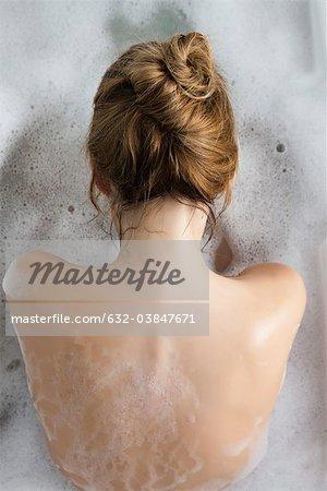 Woman relaxing in bubble bath, rear view