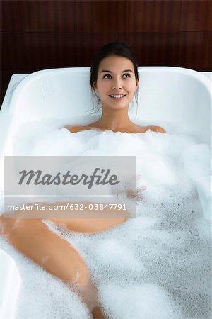 Femme se détendre dans le bain à bulles