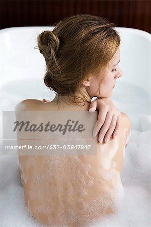 Femme se détendre dans le bain à bulles, vue arrière