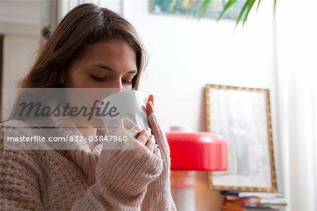 Jeune femme appréciant la tasse de café à la maison
