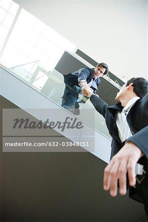 Homme d'affaires penché sur le balcon, tenant à la main du collègue