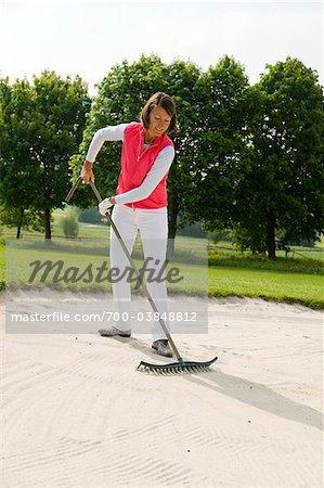 Femme ratisser le bac à sable sur le parcours de Golf