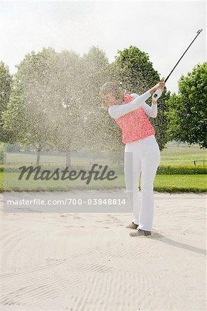 Frau im Sandkasten am Golfplatz