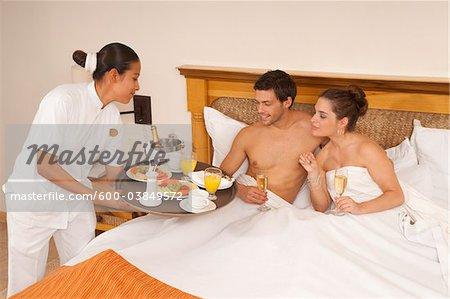 Couple étant petit déjeuner servi au lit dans l'hôtel