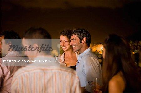 People having wine on terrace at night