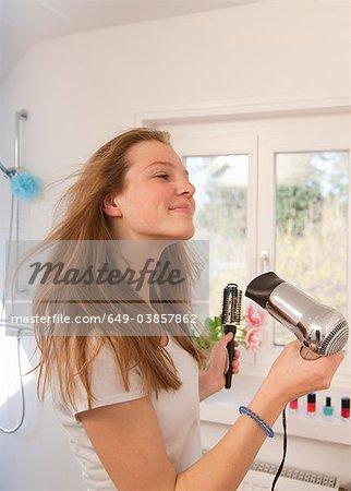 Sécher les cheveux en soufflant adolescente