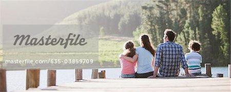 Familie sitzen auf dock, See