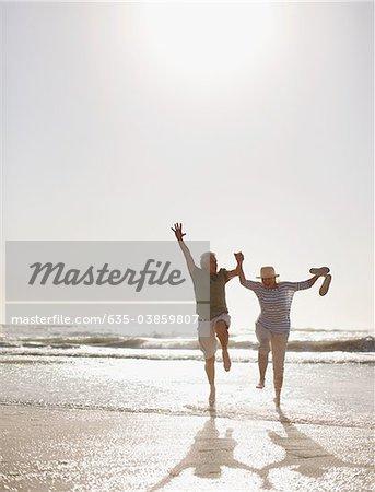 Altes Paar am Strand springen