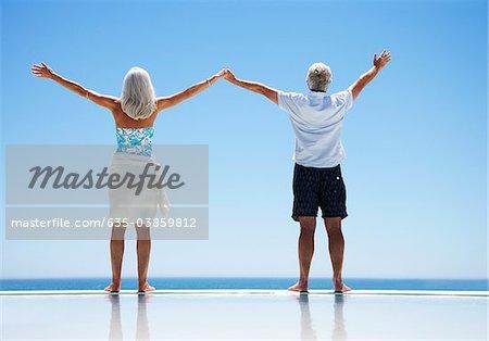 Altes Paar stehen am Rand der Infinity-Pool mit ausgestreckten