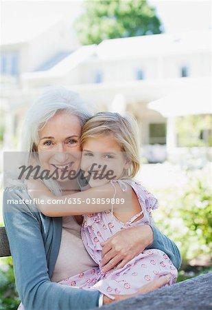 Grandmother and granddaughter hugging in garden