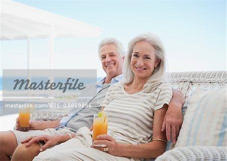 Senior couple boire des cocktails sur la terrasse de la plage