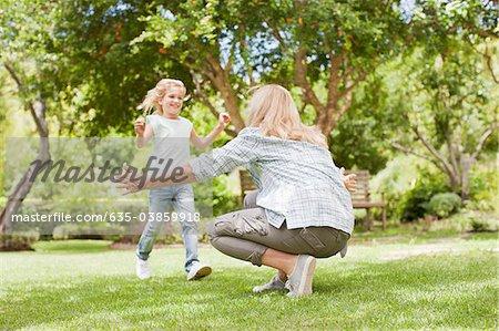 Granddaughter running toward grandmother in yard