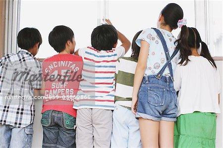 Enfants regardant dehors par une fenêtre