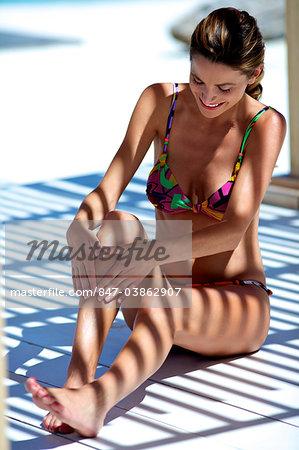 Beautiful brunette applying suncream