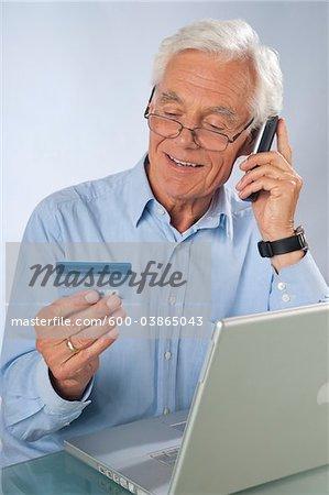 Mann mit Laptop und Schnurlostelefon