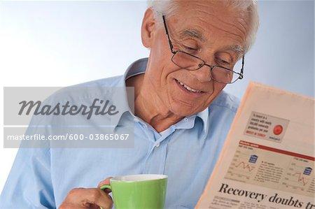 Homme boire du café et en lisant le journal