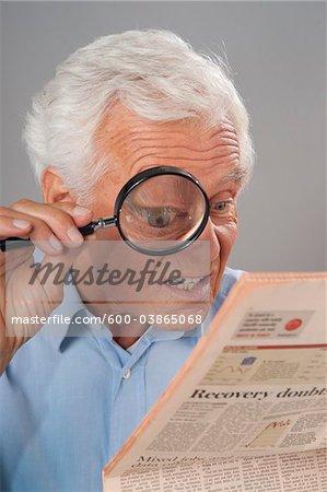 Homme regardant le journal loupe