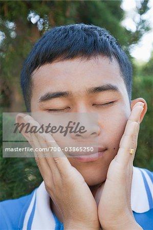 Gros plan du jeune homme de toucher le visage avec les mains
