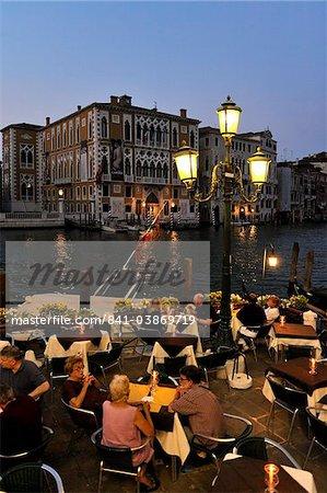 Soirée de vue d'un restaurant à côté du Grand Canal, patrimoine mondial de l'UNESCO à Venise, Vénétie, Italie, Europe