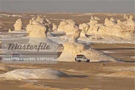 Jeeps en passant les sculptures érodées par les vents de calcium riche rocher dans le désert blanc près Baharia, Egypte, Afrique du Nord, Afrique