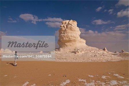 Tourist admiring unusual natural sculptures caused by wind erosion, White Desert near Bahariya, Egypt, North Africa, Africa