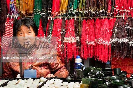 Saleswoman at coral and stone shop, Panjiayuan flea market, Chaoyang District, Beijing, China, Asia