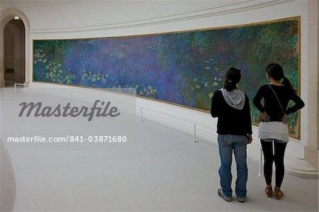 Two young women admire the Water-lilies by Claude Monet, Musee de L'Orangerie Museum, Paris, France, Europe